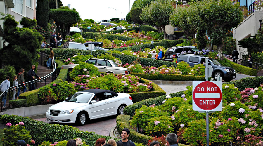 View of lombard street with cars coming down the crooked street