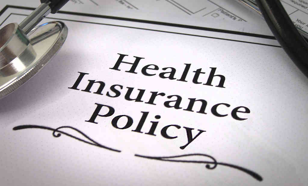 A black sign on a white card saying Health Insurance Policy and a stethoscope is placed on that card.